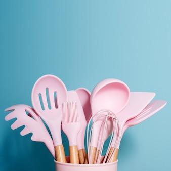 Roze keukengerei op blauw, het decorconcept van het huiskeukengereedschap, rubbertoebehoren in container. restaurant, koken, culinair, keukenthema. siliconen spatels en borstels