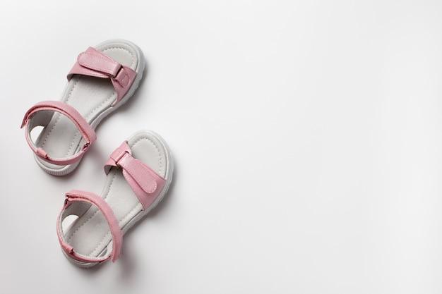 Roze kindersandalen van glanzend leer met klittenbandsluiting platte witte zolen geïsoleerd op een w...
