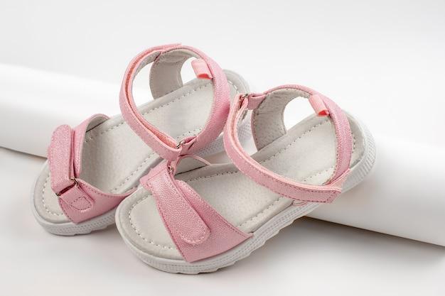 Roze kindersandalen van glanzend leer met klittenbandsluiting platte witte zolen