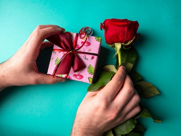 Roze klein cadeautje met een rood lint in de hand en in de andere hand een rode rozenboom op groen