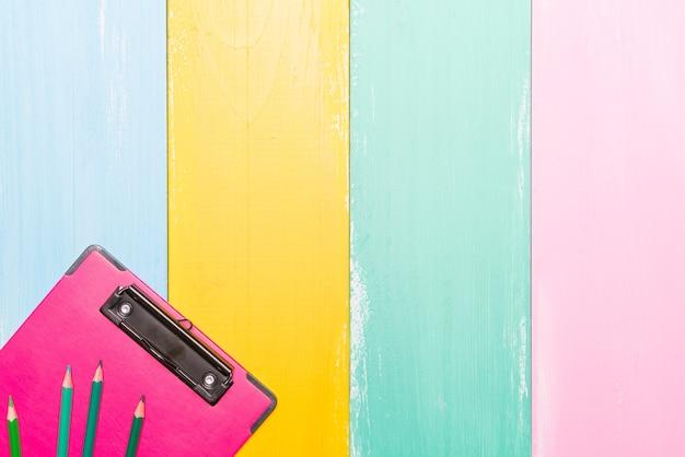 Roze klembord bovenaanzicht op kleurrijke achtergronden