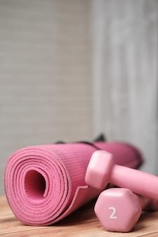 Roze kleur halter oefenmat en waterfles op wit oppervlak