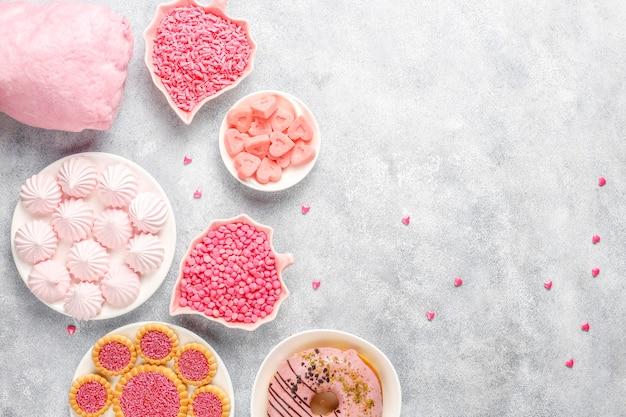 Roze kleurensnoepjes, snoepjes, meringue en suiker.