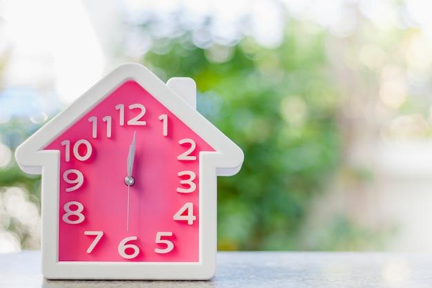 Roze klok met huisvorm bij 12 uur tegen vage natuurlijke groene achtergrond