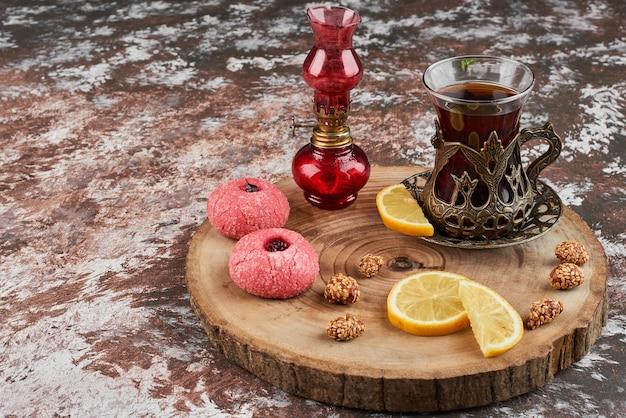 Roze koekjes en een glas thee op een houten bord.