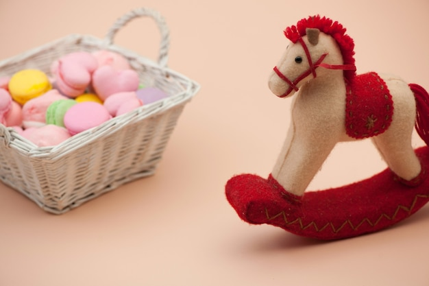 Roze koekjes en kleurrijke ronde koekjes in een rieten mand en speelgoedpaard op valentijnsdag