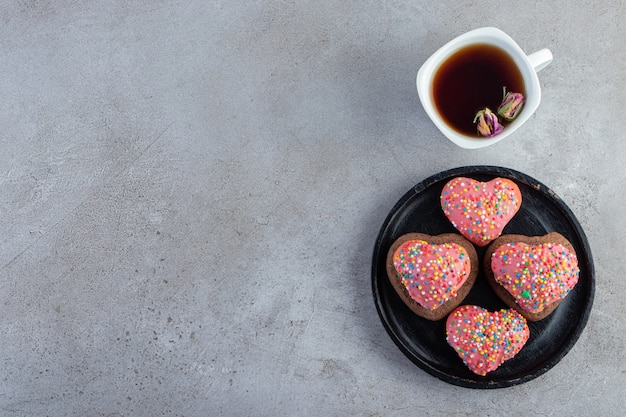 Roze koekjes in gehoorde vorm met thee op grijze achtergrond.