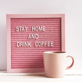 Roze koffiekop en qoute blijf thuis en drink koffie. zelfisolatie en quarantainecampagne om jezelf te beschermen en levens te redden.