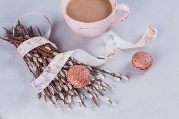 Roze koffiemok met zoete pastel franse bitterkoekjes en pussy willow op lichte tafel van bovenaf