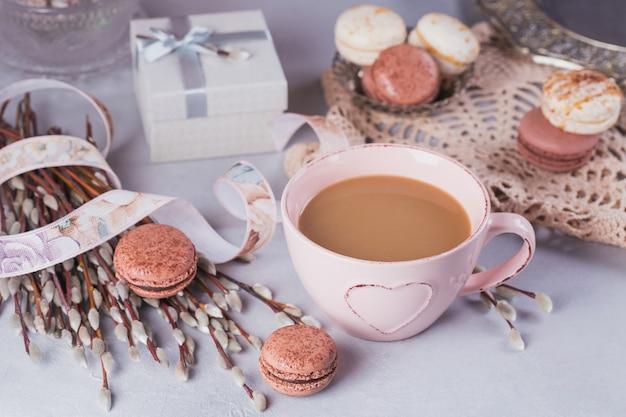 Roze koffiemok met zoete pastel franse bitterkoekjes