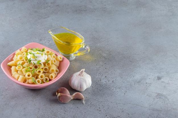 Roze kom heerlijke gekookte pasta met olijfolie op stenen achtergrond.