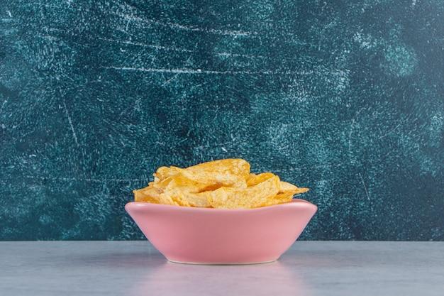 Roze kom heerlijke knapperige chips op stenen achtergrond.