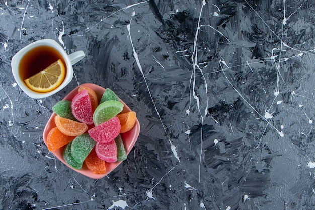 Roze kom kleurrijke marmelade met kop hete thee op marmeren oppervlak.