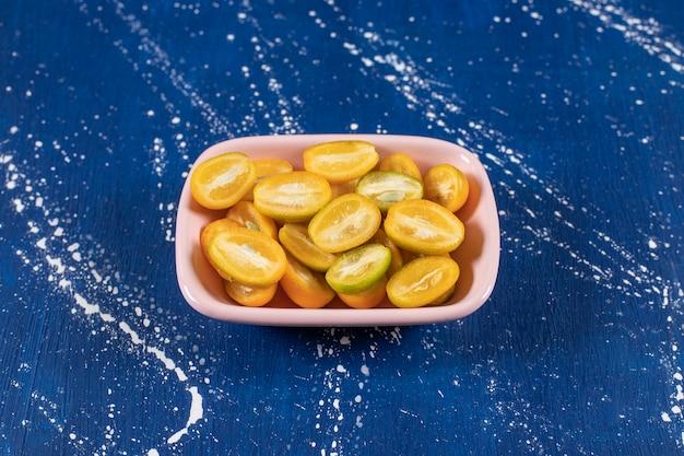 Roze kom met gesneden verse kumquatvruchten op marmeren oppervlak