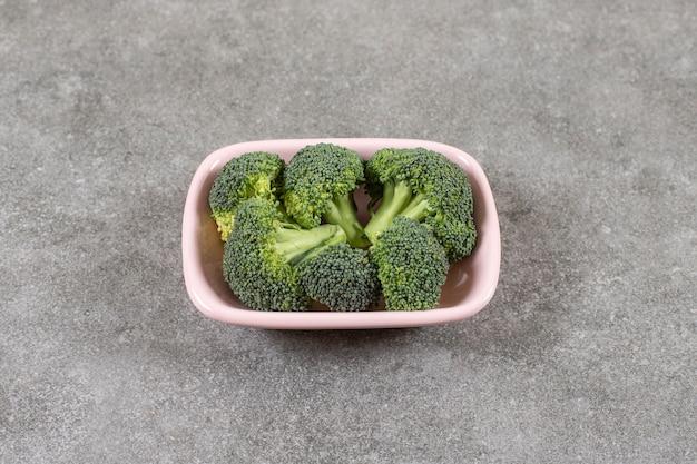 Roze kom met gezonde verse broccoli op stenen achtergrond.