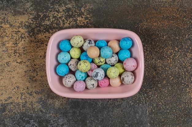 Roze kom met kleurrijke snoepjes op marmer.