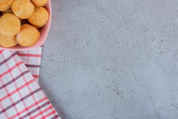 Roze kom met mini-zoete taarten op stenen tafel.