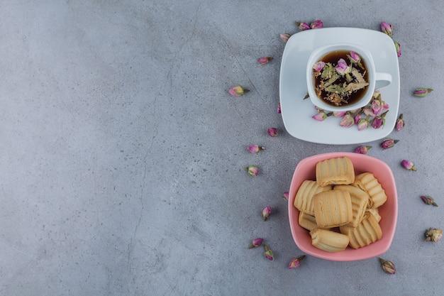 Roze kom met zoete koekjes en kop hete thee op steen.