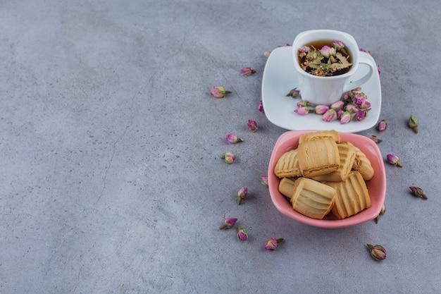 Roze kom met zoete koekjes en kopje hete thee op stenen achtergrond.
