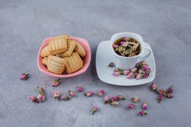 Roze kom met zoete koekjes en kopje hete thee op stenen oppervlak.