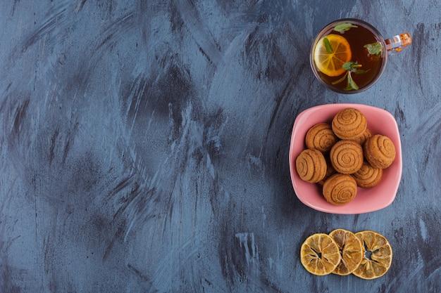 Roze kom mini kaneelcakes met glas thee op steen.