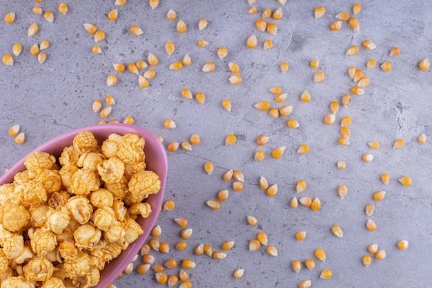 Roze kom zoute popcorn op stenen oppervlak