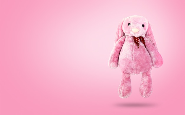 Roze konijnpop met afluisteraar op zoete achtergrond. leuk knuffeldier en pluizig bont voor kinderen.