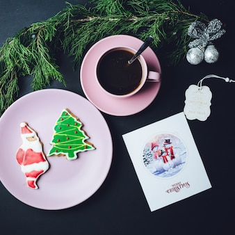 Roze kop koffie, bord met kerstmisbroodjes en briefkaart liggen op zwarte tafel