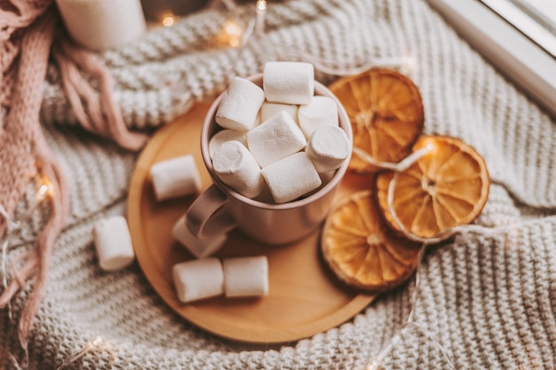 Roze kop met marshmallows op een houten dienblad en citrus plakjes