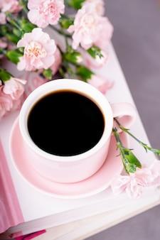 Roze kopje zwarte koffie en pastel roze anjerbloemen