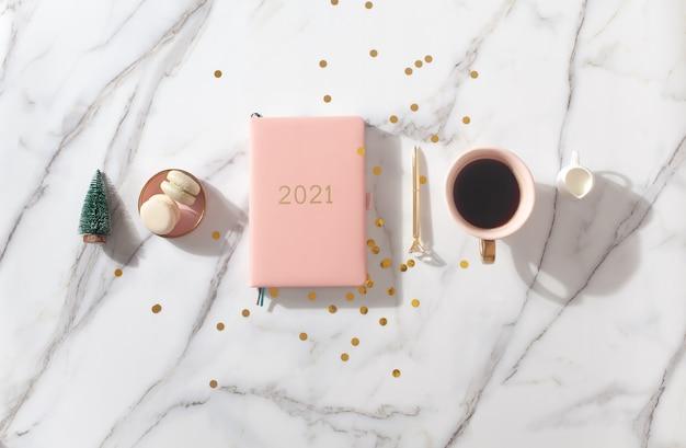 Roze koraalkleurige agenda voor het jaar 2021 met koffie en bitterkoekjes