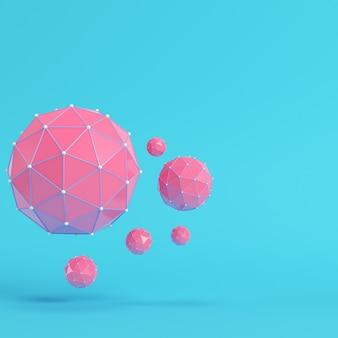 Roze laag poly abstracte bollen op heldere blauwe achtergrond