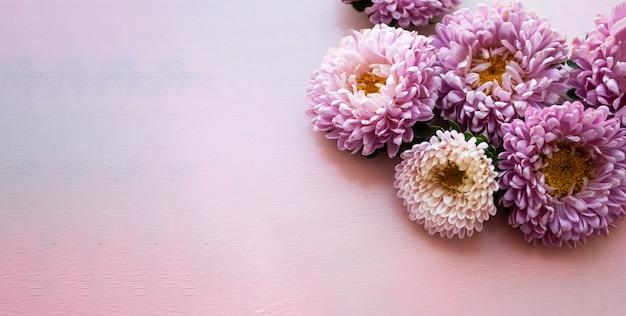 Roze lange houten banner waarop roze asterbloemen liggen. plaats voor tekst.