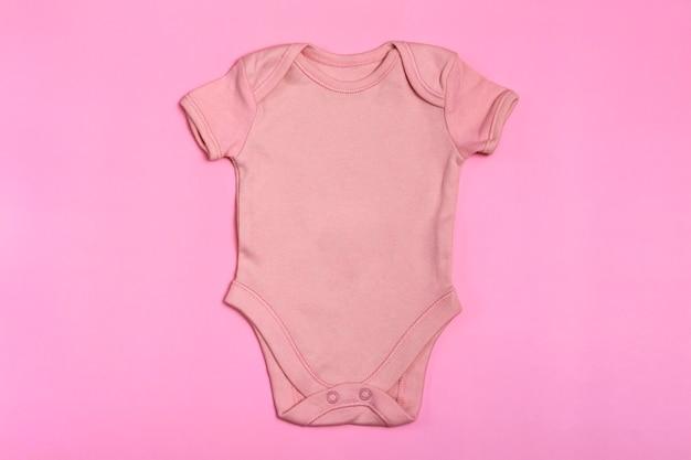 Roze lege baby romper sjabloon, mock up close-up op roze achtergrond. babyromper, jumpsuit voor pasgeborenen. uitzicht van boven
