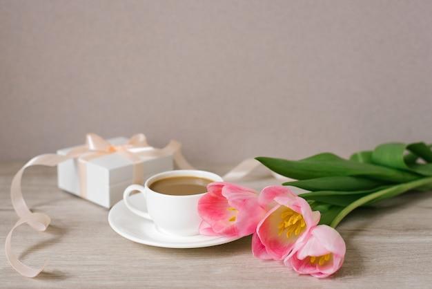 Roze lentetulpen, een geschenkdoos en een kopje koffie. het concept van vrouwendag of moederdag. lentefestival