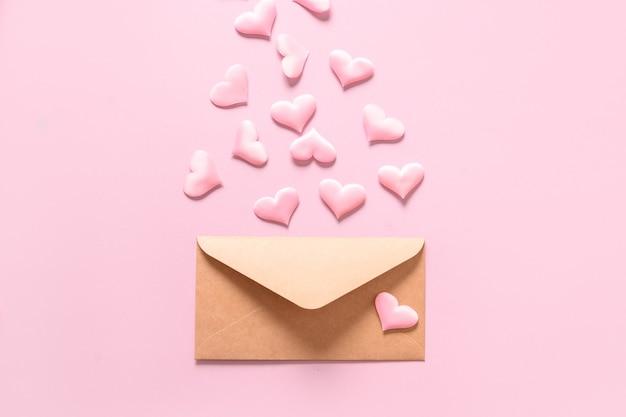 Roze liefdeharten van envelop op roze achtergrond. valentijnsdag wenskaart met kopie ruimte.