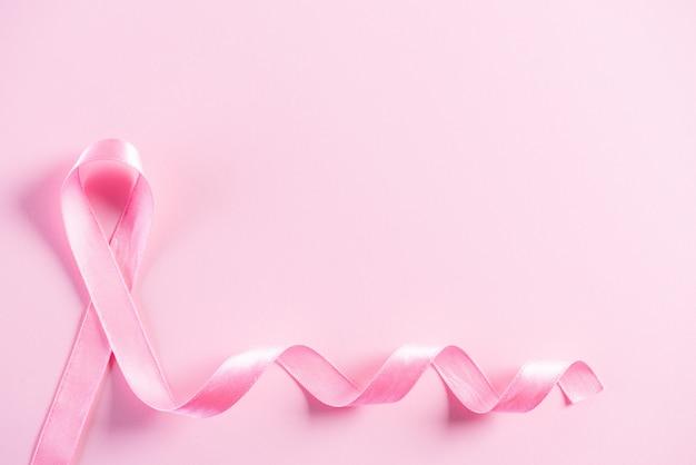 Roze lint op roze pastel papier ter ondersteuning van het bewustzijn van borstkanker