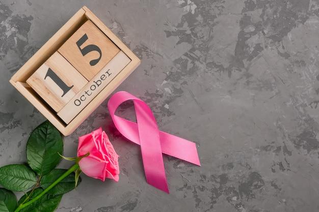 Roze lint, roos en houten kubus kalender ingesteld voor 15 oktober op betonnen ondergrond.