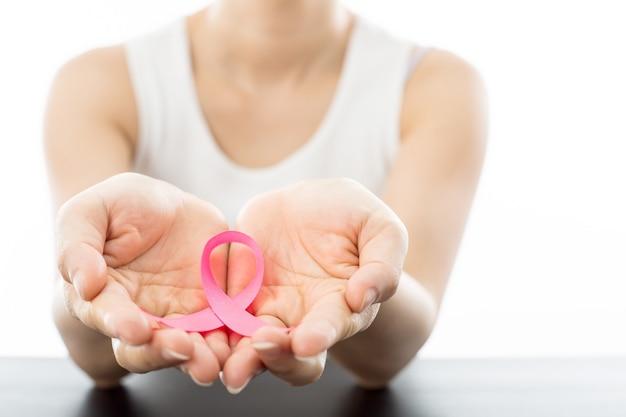 Roze lint voor het bewustzijn van borstkanker door een vrouw die het gezondheidszorgconcept moet tonen.