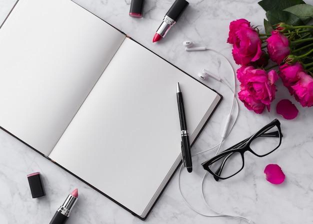 Roze lippenstift, hoofdtelefoons, glazen en rozenboeket met lege blocnote op wit