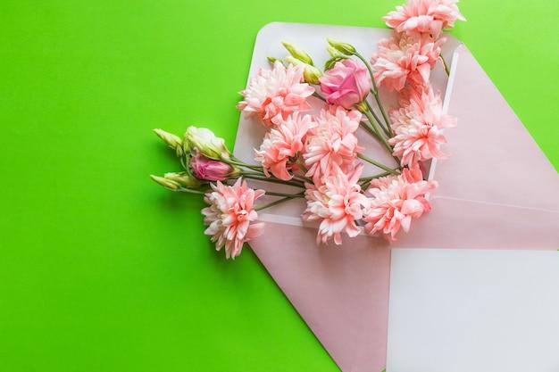Roze lisianthus en chrysanten in envelop op groene achtergrond. moederdag, huwelijksuitnodiging.