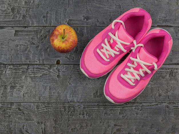 Roze loopschoenen voor fitnesslessen in de sportschool en een rijpe appel op een houten vloer.