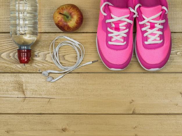 Roze loopschoenen voor fitnesslessen in de sportschool en een rijpe appel op een vloer. uitzicht van boven.