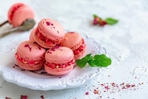 Roze macaroni met crème bloemen en rozenblaadjes.