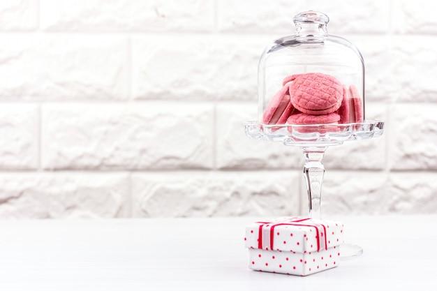 Roze macaronkoekjes in een kristallen vaas en een geschenkdoos