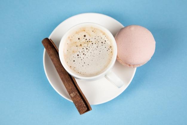 Roze macarons en koffie met kaneel op een blauwe ondergrond