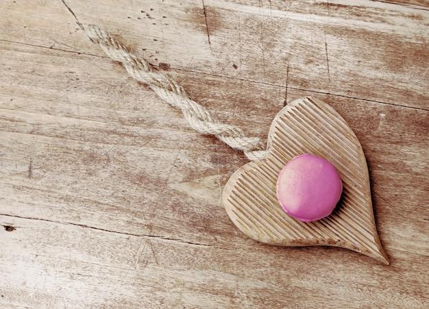 Roze macarroon op houten hart