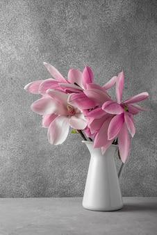 Roze magnolia bloemen boeket in vaas op grijze betonnen ondergrond