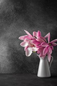 Roze magnolia bloemen boeket in vaas op zwarte ondergrond