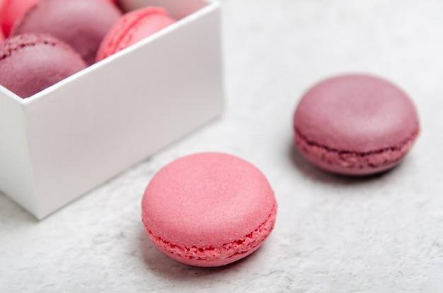 Roze makaronkoekjes op een steenachtergrond in doos. het concept van snoep, gebak, junkfood. minimale compositie.